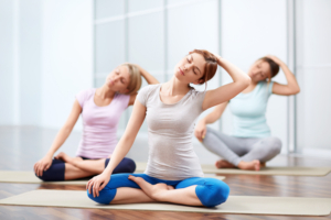 Group of women in yoga class stretching necks